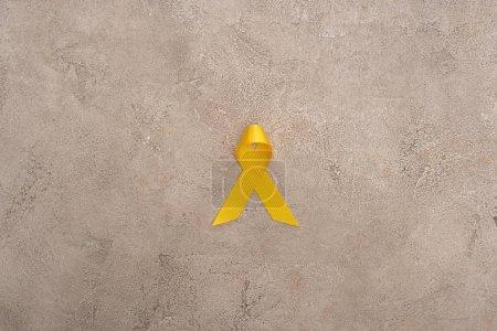 Photo pour Vue du dessus du ruban jaune sur fond gris, concept de journée internationale contre le cancer chez les enfants - image libre de droit