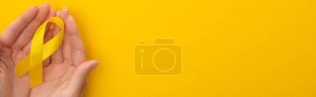 Photo pour Vue recadrée des mains féminines avec ruban jaune sur fond coloré, prise de vue panoramique, concept de journée internationale contre le cancer chez les enfants - image libre de droit