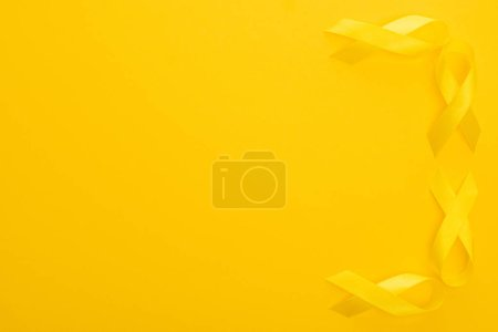 Photo for Top view of yellow ribbons on colorful background, international childhood cancer day concept - Royalty Free Image
