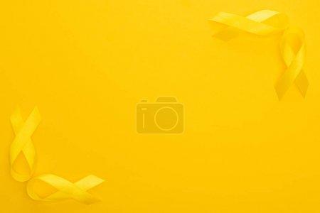 Foto de Visión superior de las cintas amarillas sobre fondo colorido, concepto internacional de Día Internacional del Cáncer Infantil. - Imagen libre de derechos