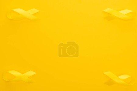 Photo pour Lit plat avec rubans de sensibilisation jaunes sur fond coloré, concept de la Journée internationale du cancer chez les enfants - image libre de droit
