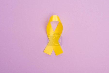 Photo pour Vue du dessus du ruban jaune sur fond violet, concept de journée internationale contre le cancer chez les enfants - image libre de droit