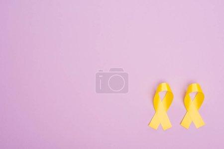 Foto de Acostado plano con cintas de conciencia amarillas sobre fondo violeta, concepto de día internacional del cáncer infantil - Imagen libre de derechos