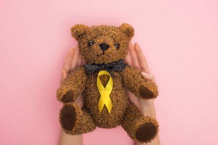 Photo pour Vue recadrée d'une femme tenant un ours en peluche avec un ruban jaune sur fond rose, concept de journée internationale contre le cancer chez l'enfant - image libre de droit