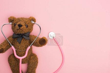 Photo pour Vue du dessus du stéthoscope avec ours en peluche sur fond rose, concept de journée internationale contre le cancer chez l'enfant - image libre de droit