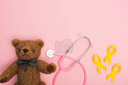 Photo pour Vue de dessus des rubans jaunes à côté du stéthoscope et de l'ours en peluche sur fond rose, concept de journée internationale contre le cancer chez les enfants - image libre de droit