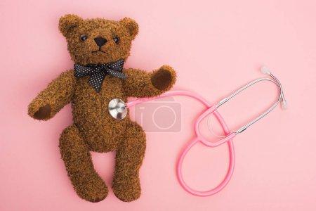 Photo pour Vue d'ensemble du stéthoscope relié à l'ours en peluche sur fond rose, concept de journée internationale contre le cancer chez l'enfant - image libre de droit
