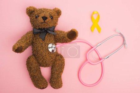 Photo pour Vue en haut du ruban jaune et du stéthoscope reliés à l'ours en peluche sur fond rose, concept de la Journée internationale du cancer chez les enfants - image libre de droit