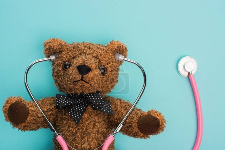 Top view of brown teddy bear with pink stethoscope on blue background, international childhood cancer day concept