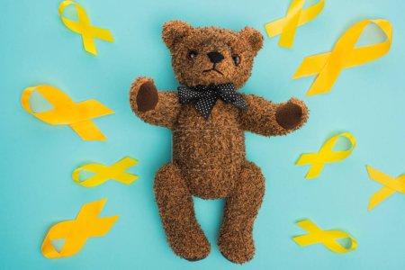 Photo pour Vue du dessus des rubans jaunes et de l'ours en peluche brun avec arc sur fond bleu, concept de journée internationale contre le cancer chez les enfants - image libre de droit