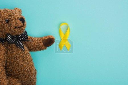 Photo pour Vue du dessus de l'ours en peluche avec arc et ruban jaune sur fond bleu, concept de journée internationale contre le cancer chez les enfants - image libre de droit