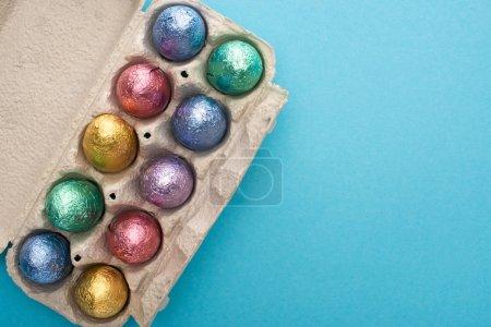 Draufsicht auf Schokolade-Ostereier in Eierschale auf blauem Hintergrund