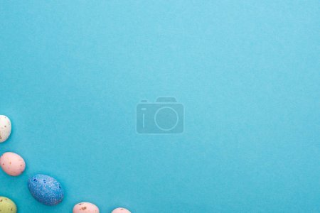 Photo for Top view of colorful chicken and quail eggs on blue background - Royalty Free Image
