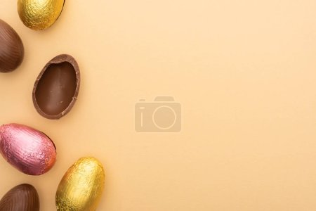 Photo for Top view of delicious chocolate eggs on beige background - Royalty Free Image