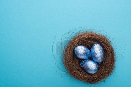 Photo for Top view of chocolate Easter eggs inside nest on blue background - Royalty Free Image