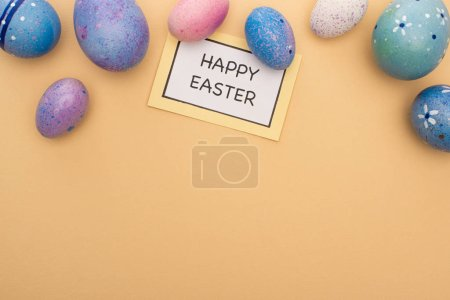 Top view of card with happy easter lettering and Easter eggs on beige background