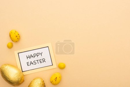 Top view of card with happy easter lettering, candies, yellow quail and chocolate eggs on beige background