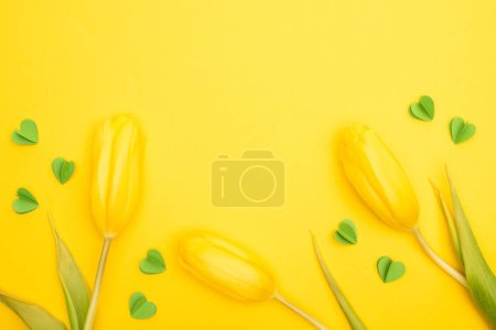 Photo for Top view of tulips and decorative green hearts on yellow background, spring concept - Royalty Free Image