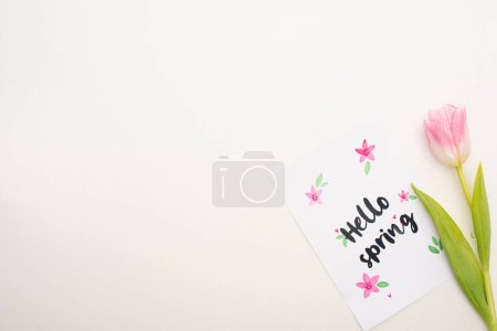 Photo for Top view of pink tulip near card with hello spring lettering on white background - Royalty Free Image