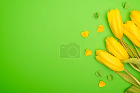 Photo for Top view of yellow tulips and decorative hearts on green, spring concept - Royalty Free Image