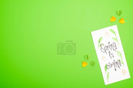 Photo pour Vue du dessus de la carte avec le printemps est à venir lettrage et cœurs décoratifs colorés sur fond vert - image libre de droit