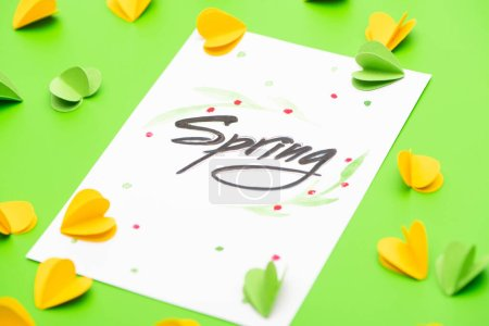 Photo for Selective focus of card with spring lettering and decorative hearts on green background - Royalty Free Image