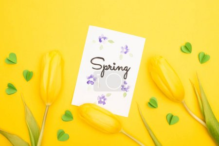 Photo for Top view of tulips, card with spring lettering and decorative green hearts on yellow background - Royalty Free Image