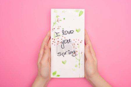 Photo pour Vue partielle de la femme tenant la carte avec je t'aime lettrage de printemps sur fond rose - image libre de droit