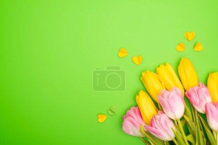Photo pour Vue en haut des tulipes jaunes et roses avec cœurs décoratifs sur fond vert, concept du printemps - image libre de droit
