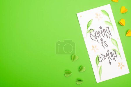 Photo for Top view of card with spring is coming lettering and decorative hearts on green background - Royalty Free Image