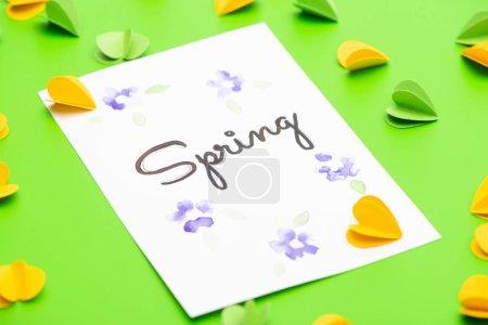 Photo pour Mise au point sélective de la carte avec lettrage printanier et cœurs décoratifs sur fond vert - image libre de droit