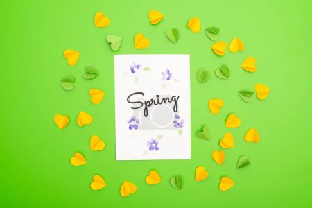 Photo for Top view of card with spring lettering with decorative hearts on green background - Royalty Free Image