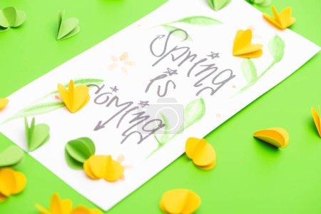 Photo pour Mise au point sélective de la carte avec le printemps est à venir lettrage et les cœurs décoratifs sur fond vert - image libre de droit