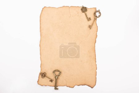 Photo for Top view of vintage keys on aged paper isolated on white - Royalty Free Image