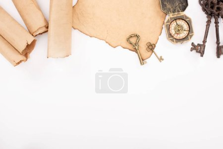 Photo pour Vue de dessus des clés vintage et boussole sur papier vieilli isolé sur blanc - image libre de droit