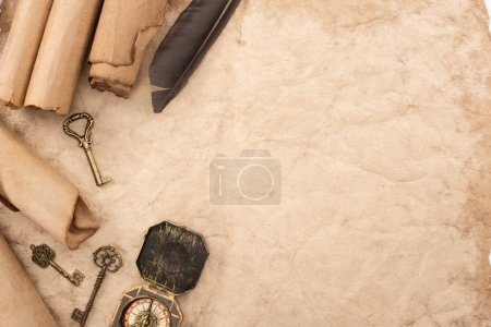Photo for Top view of vintage keys and compass near feather on aged paper - Royalty Free Image