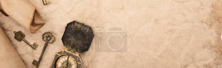 Photo for Top view of vintage keys and compass on aged paper, panoramic shot - Royalty Free Image