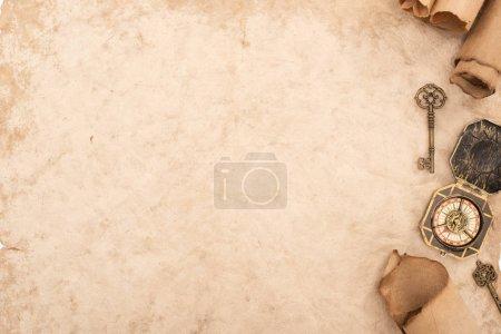 Photo pour Vue de dessus des clés vintage et boussole sur papier vieilli - image libre de droit