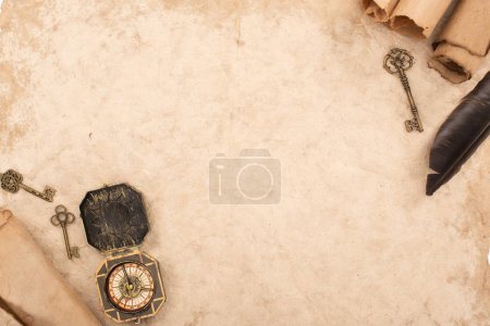 Photo for Top view of feather, vintage keys and compass on aged paper - Royalty Free Image