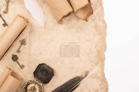 Foto de Vista superior de plumas, llaves vintage y brújula sobre papel antiguo aislado sobre blanco. - Imagen libre de derechos