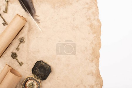 Photo pour Top view of feather, vintage keys and compass on aged paper isolated on white - image libre de droit