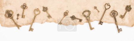Photo for Top view of vintage keys on aged paper isolated on white, panoramic shot - Royalty Free Image
