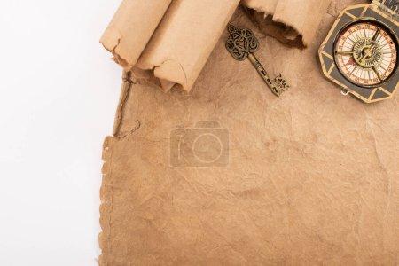 Photo pour Vue de dessus de la clé vintage et boussole sur papier vieilli isolé sur blanc - image libre de droit