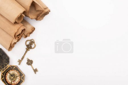 Photo for Top view of vintage keys, compass and rolled aged paper isolated on white - Royalty Free Image