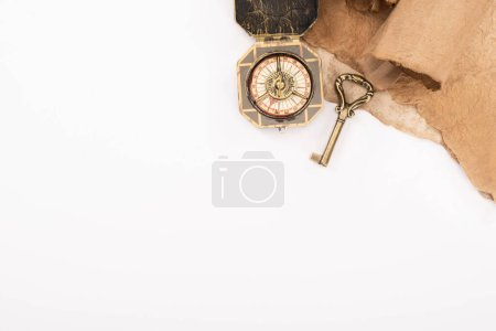 Photo for Top view of vintage key, compass and aged paper isolated on white - Royalty Free Image