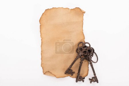Photo for Top view of vintage keys on aged empty paper isolated on white - Royalty Free Image