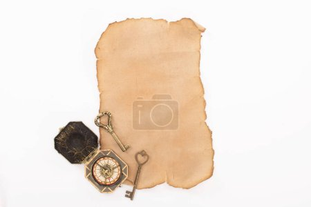 Photo for Top view of vintage compass, keys on aged paper isolated on white - Royalty Free Image