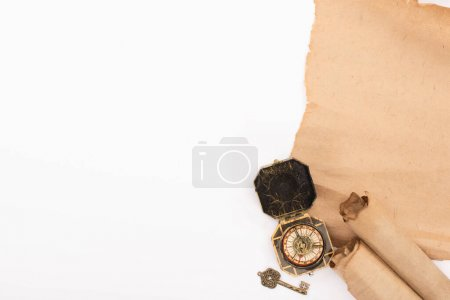 Photo for Top view of vintage compass, key and aged parchment paper isolated on white - Royalty Free Image