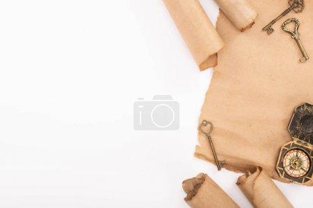 Foto de Vista superior de la brújula, llaves y papel pergamino antiguo aislado sobre blanco. - Imagen libre de derechos