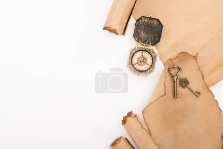Photo for Top view of vintage compass, keys and aged parchment paper isolated on white - Royalty Free Image